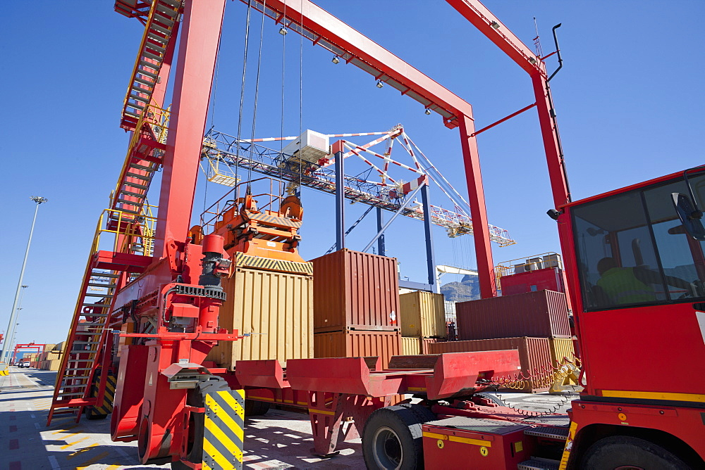 Crane loading cargo container onto lorry at commercial dock