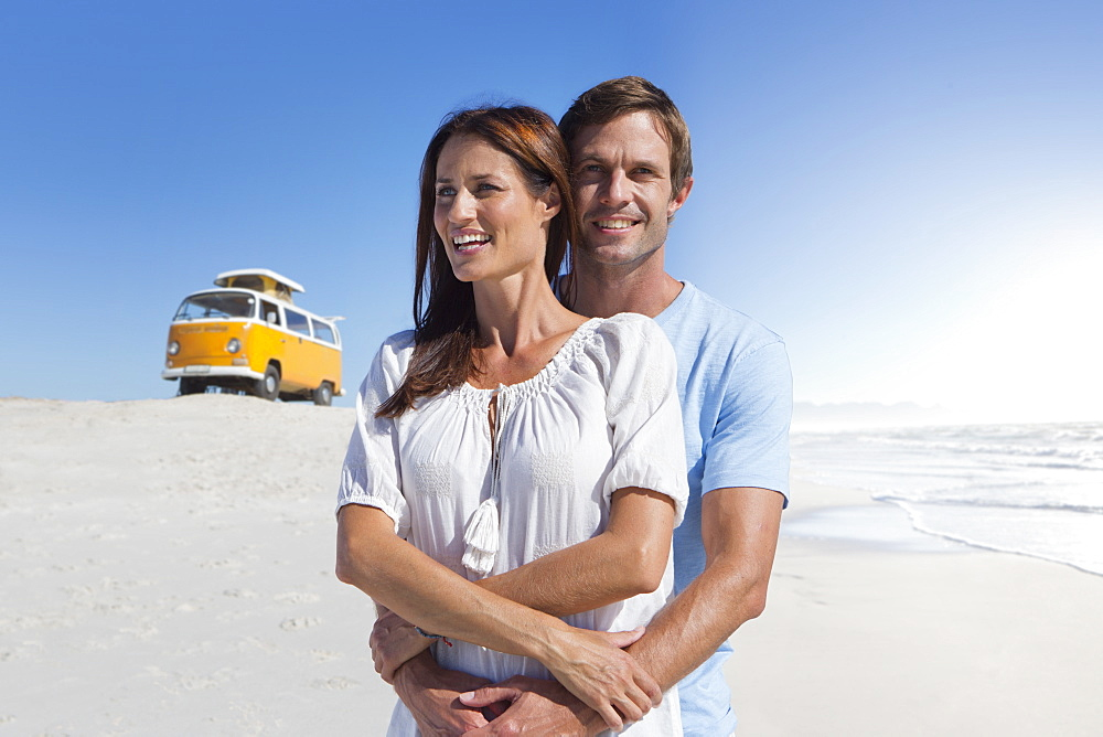Happy couple hugging on sunny beach with van in background