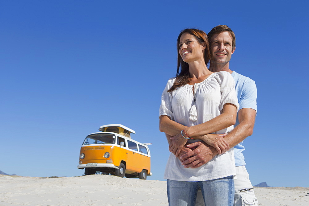 Happy couple holding hands on sunny beach with van in background