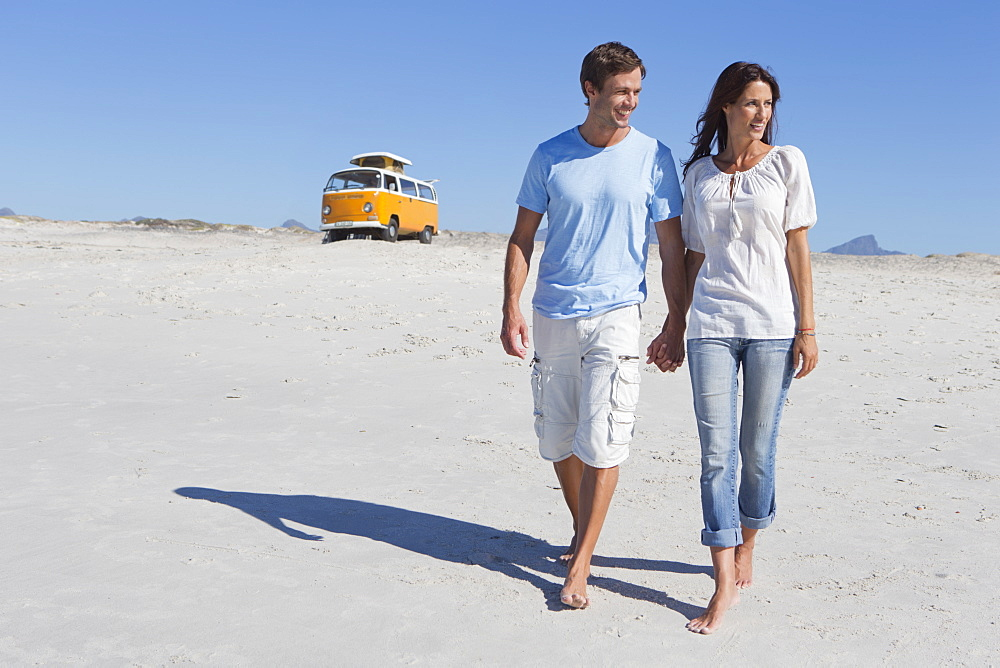 Couple holding hands and walking on beach with van in background