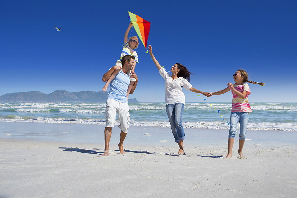 Happy family flying kite on sunny beach