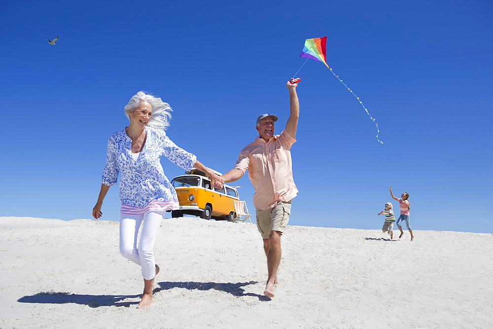 Grandparents and grandchildren running with kite on sunny beach with van in background