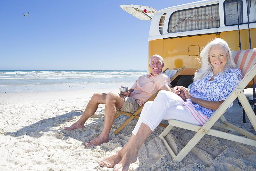 Portrait of smiling senior couple sitting on lounge chairs on sunny beach near van
