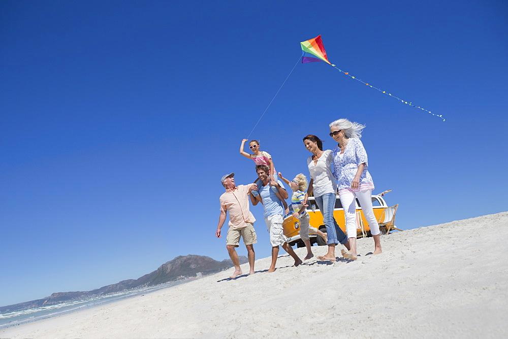 Happy multi-generation family with kite walking on sunny beach