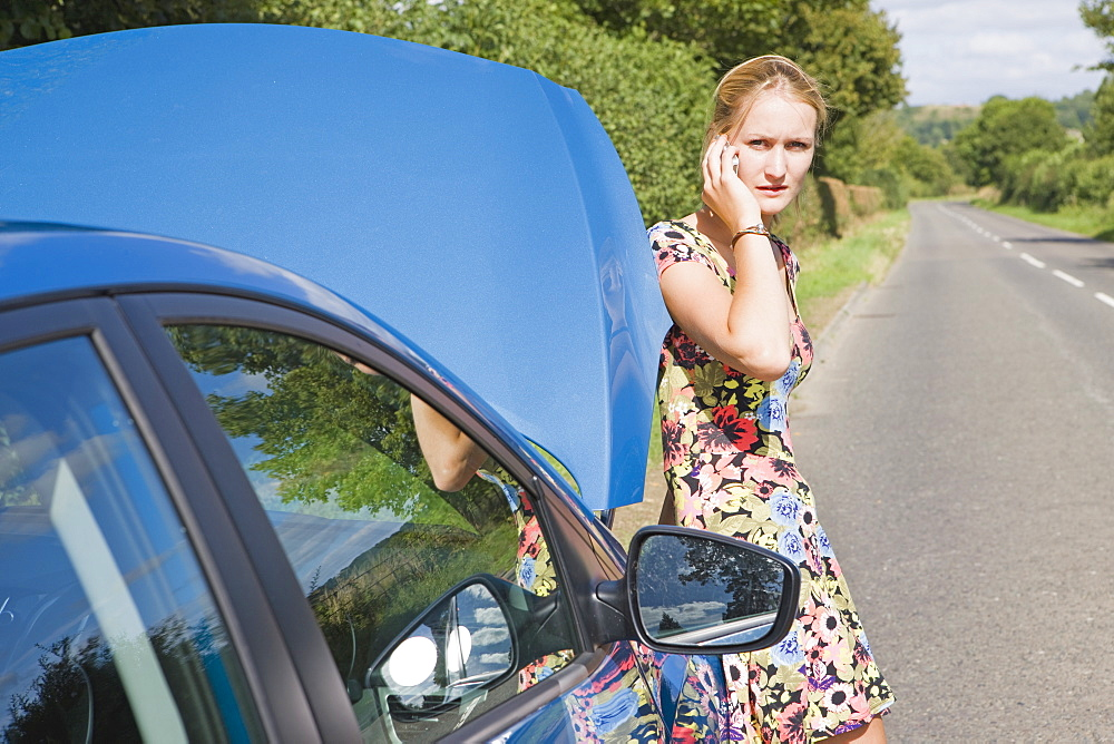 Woman With Broken Down Car Phoning For Assistance