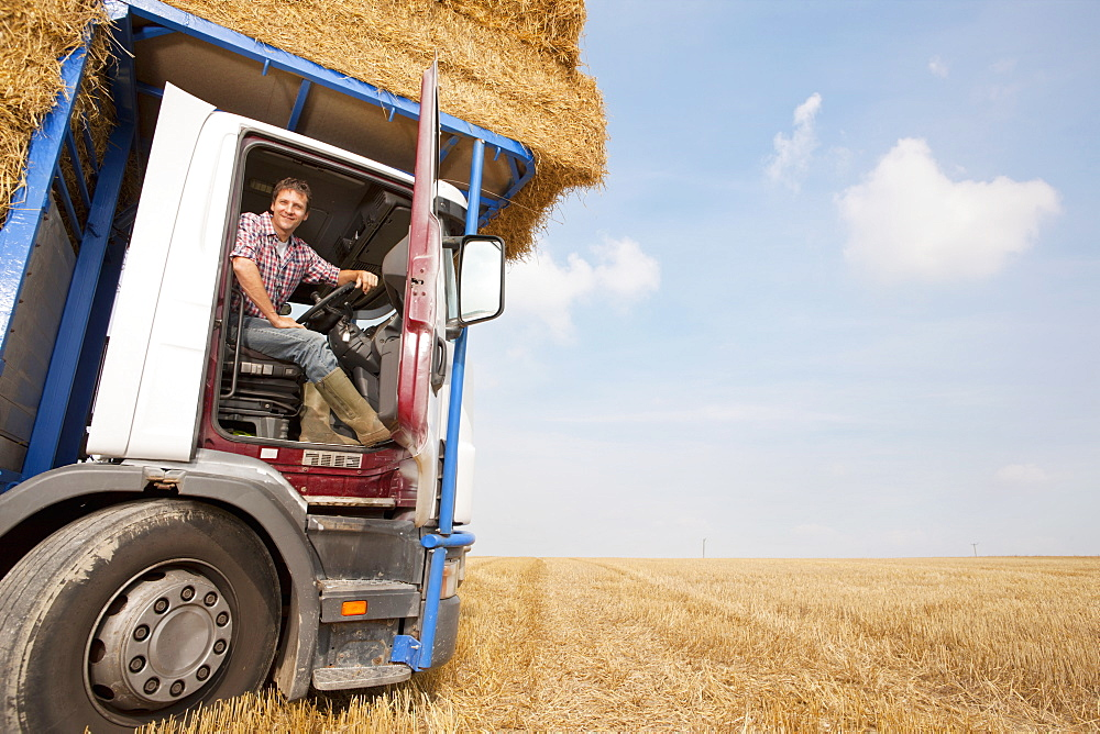 Farmer Driving Lorry Loaded With Straw Bales In Field