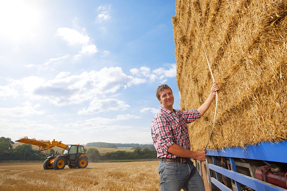 Farmer Securing Straw Bales Onto Lorry