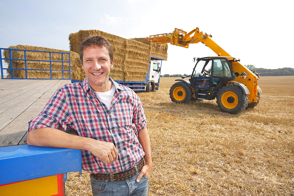 Farmer Supervising Straw Bales Being Loaded Onto Lorry