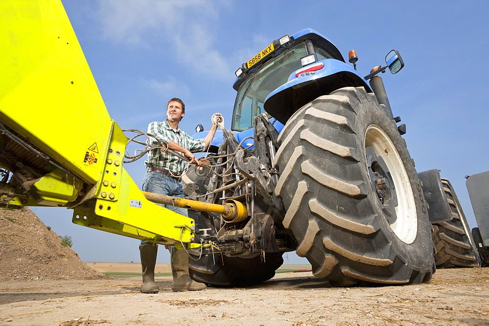 Farmer Attaching Farm Equipment To Tractor - 786-9457