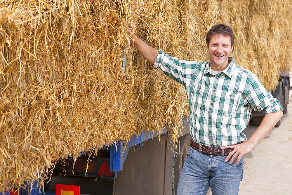Farmer Standing Next To Lorry Loaded With Straw Bales