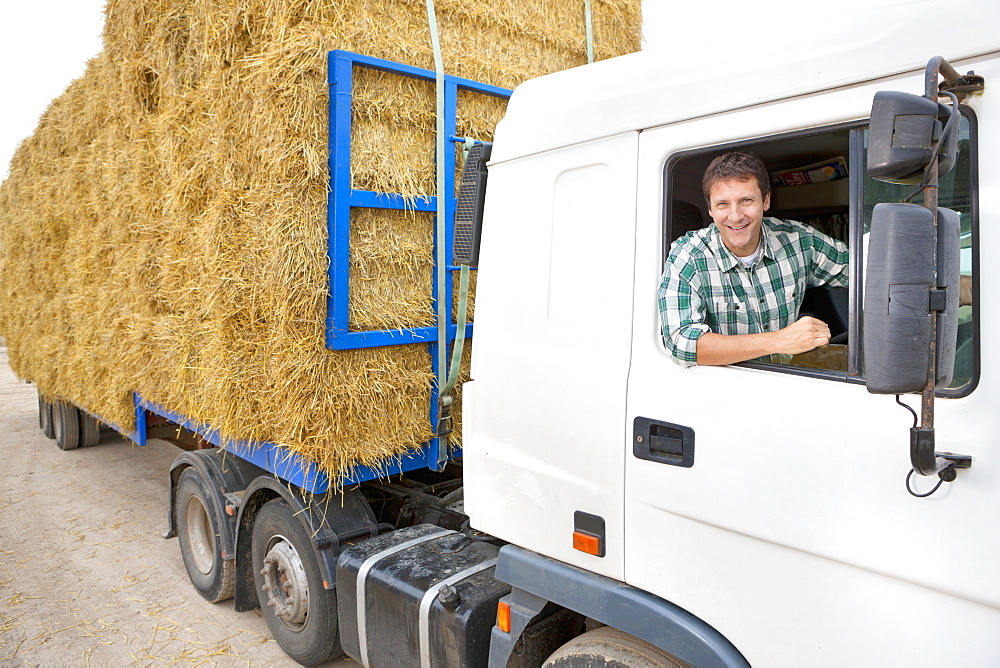 Farmer Driving Lorry Loaded With Straw Bales