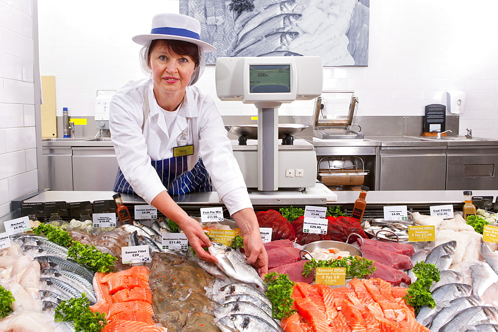 Female Fishmonger In Fresh Fish Department Of Supermarket