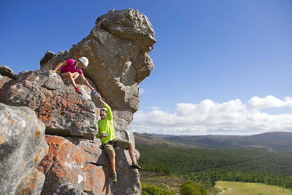 Male rock climber handing water bottle to woman on top of rock