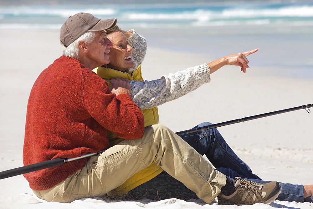 Happy senior couple with fishing rod sitting on sunny beach