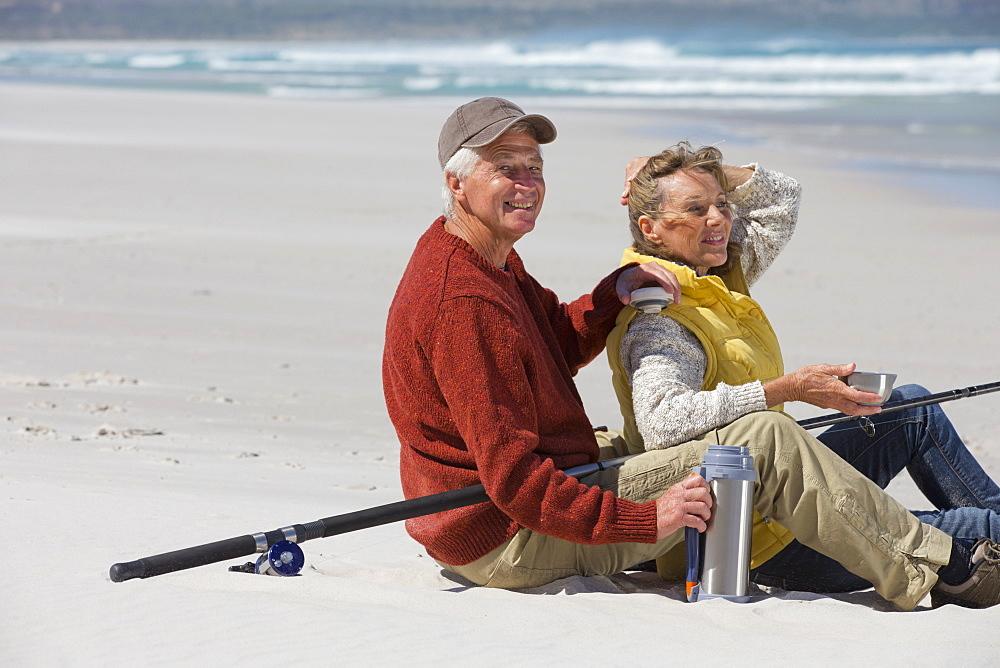 Senior couple with fishing rod drinking coffee on sunny beach