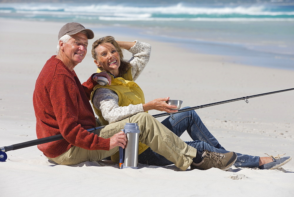 Portrait of smiling senior couple with fishing rod drinking coffee on sunny beach