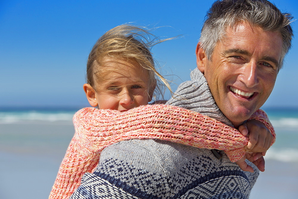 Close up portrait of smiling father piggybacking daughter on sunny beach