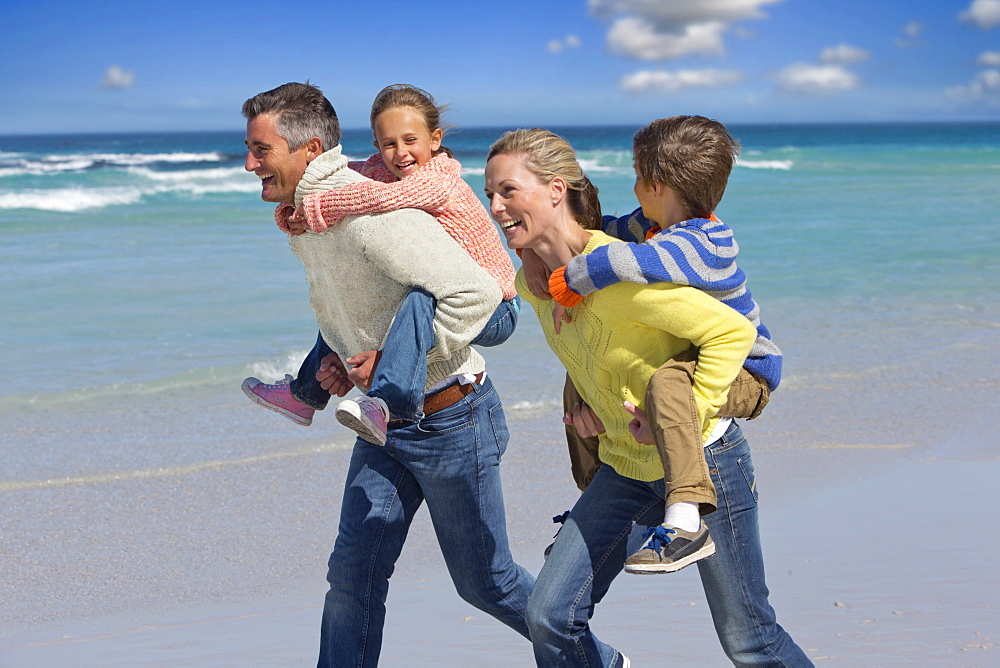 Happy parents piggybacking on sunny beach