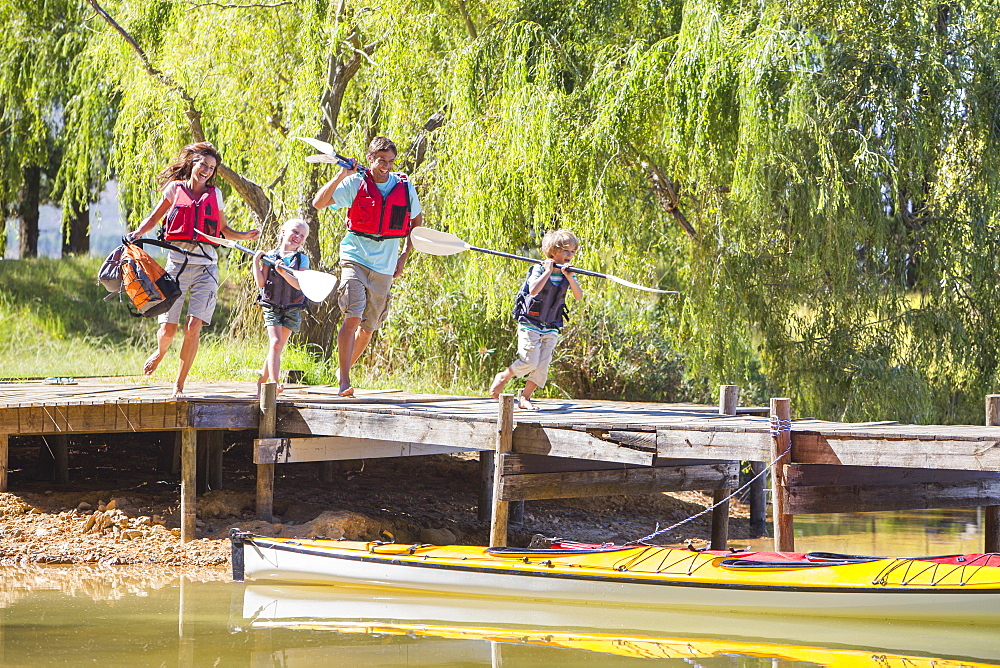 Enthusiastic family running with oars on dock