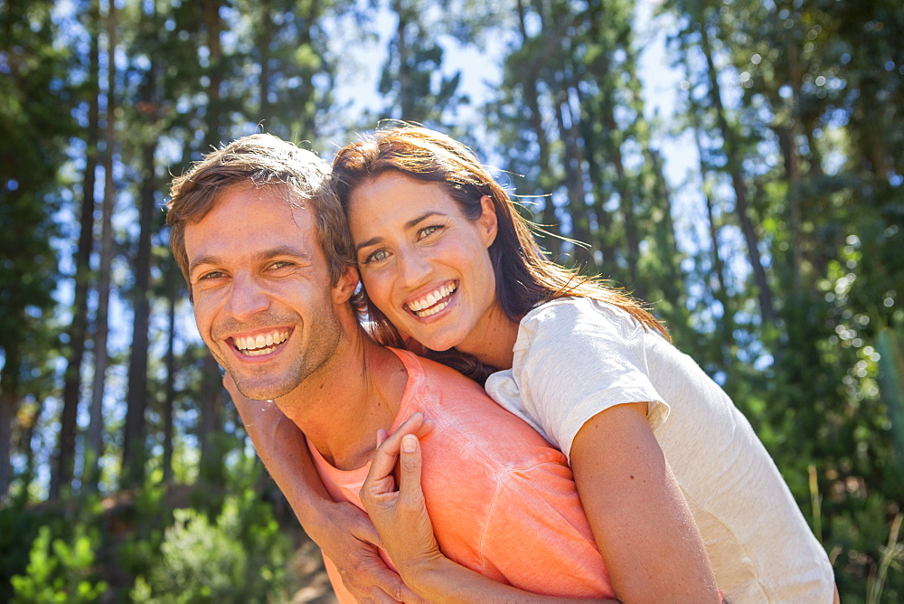 Portrait of enthusiastic couple piggybacking in woods