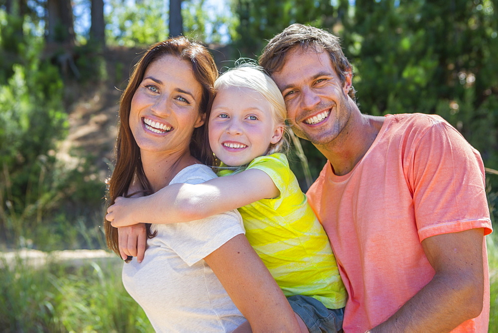Portrait of enthusiastic family in woods