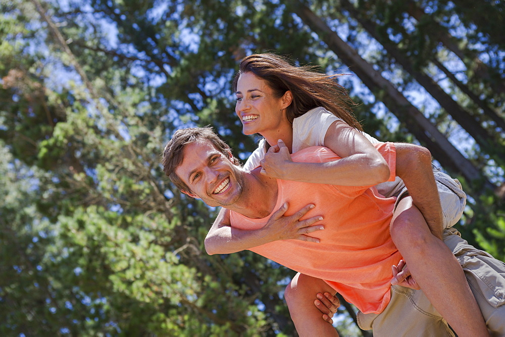 Portrait of smiling man piggybacking woman in woods