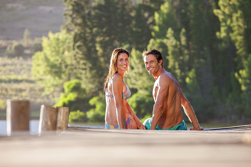 Portrait of smiling couple sitting at the edge of dock over lake