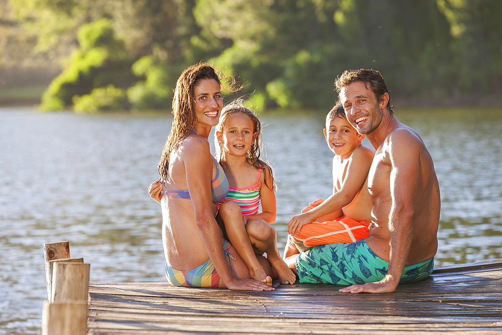 Portrait of happy family sitting at the edge of dock over lake