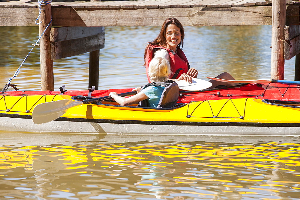 Mother and daughter in kayaks on lake