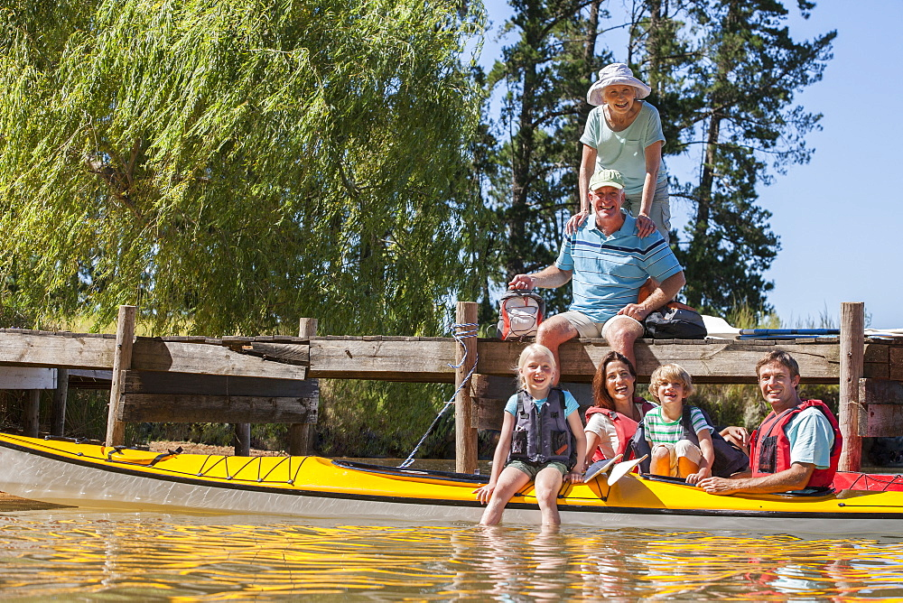 Portrait of multi-generation family on dock and in kayaks on lake