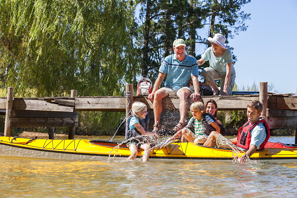 Multi-generation family on dock and in kayaks on lake
