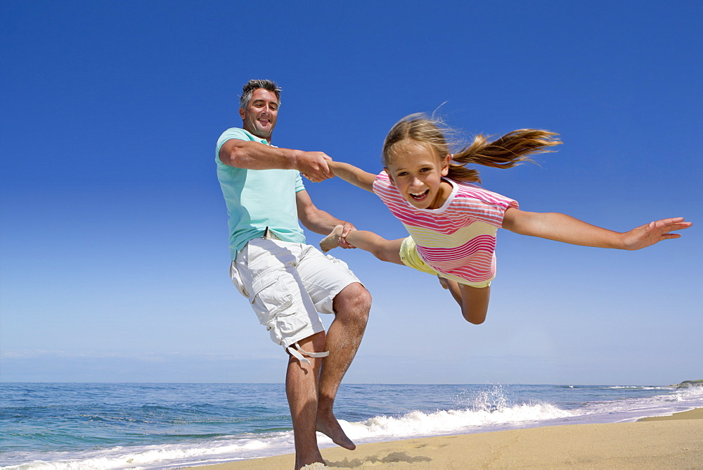 Father spinning daughter on sunny beach