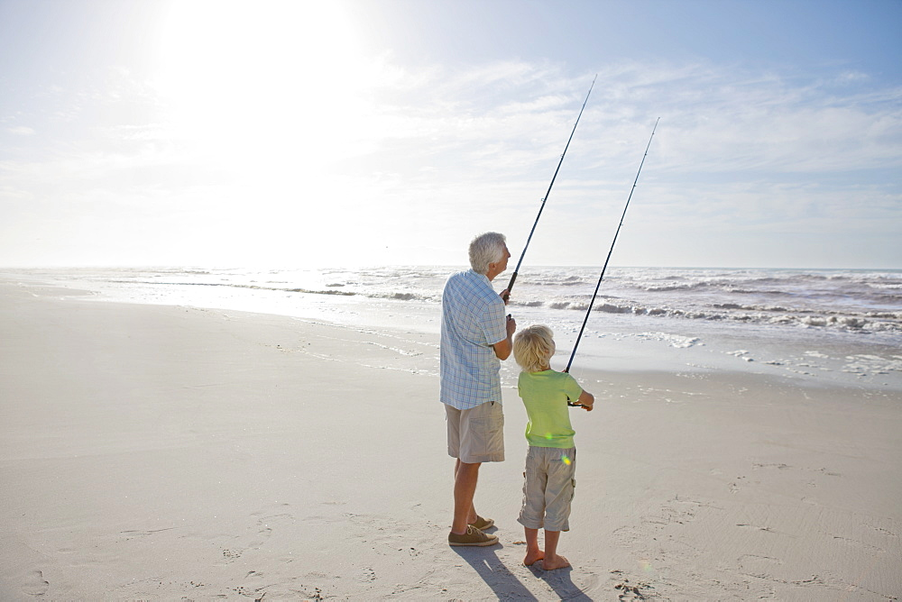 Grandfather and grandson fishing on sunny beach