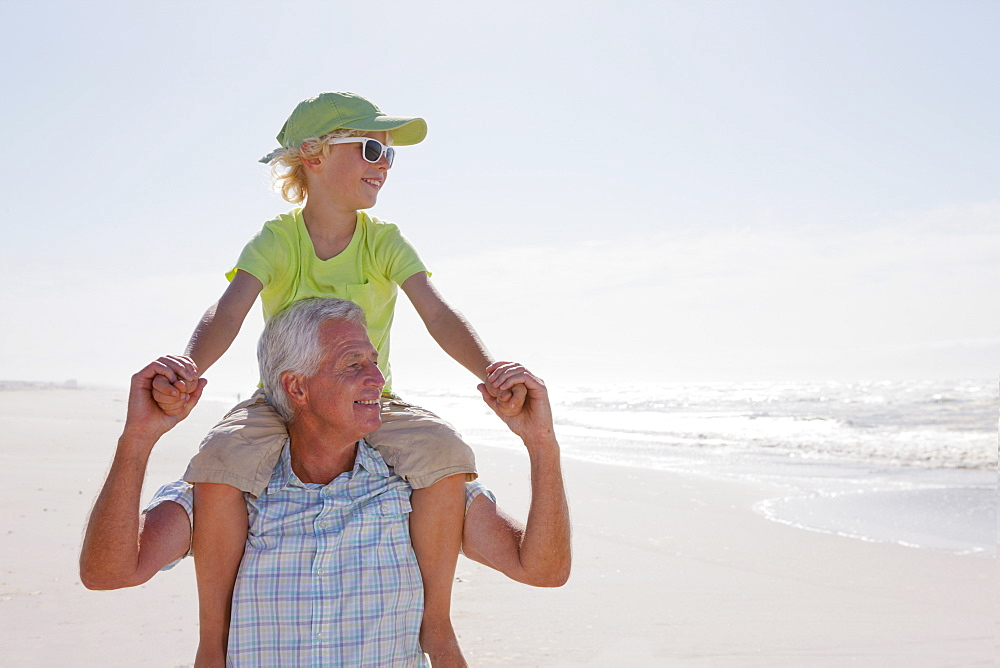 Smiling grandfather carrying grandson on shoulders on sunny beach