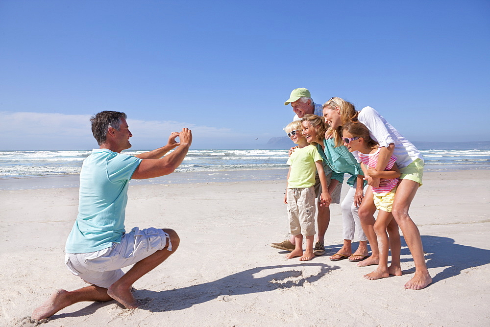 Father with digital camera photographing multi-generation family on sunny beach