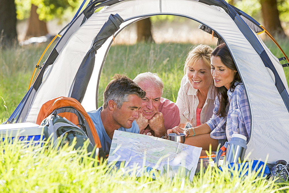 Adult Family Group Enjoying Camping Holiday In Countryside
