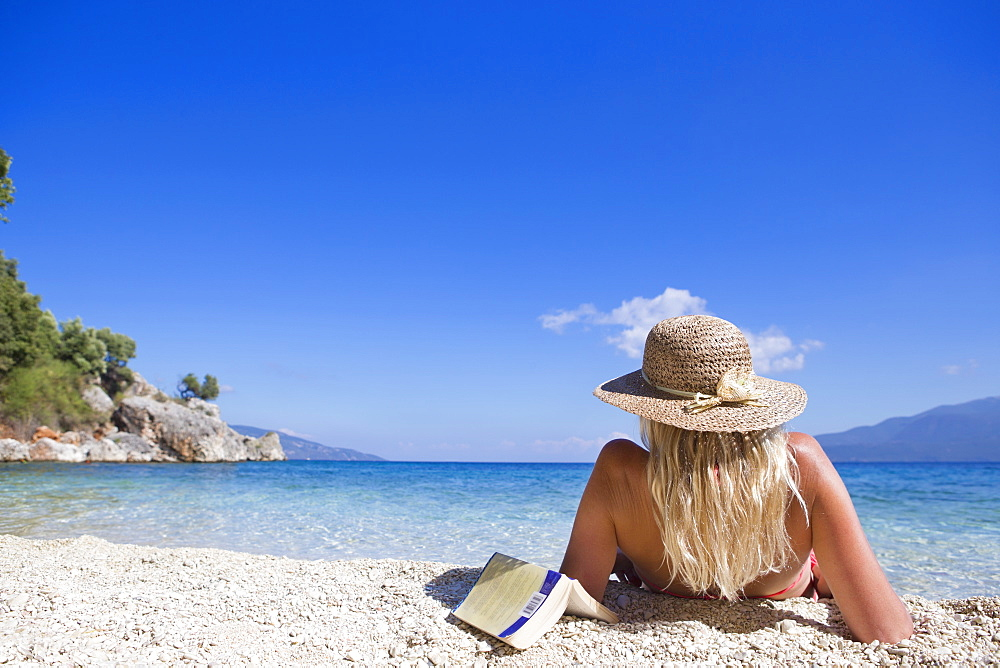 woman, looking out to sea, lying on beach with book - 786-9982