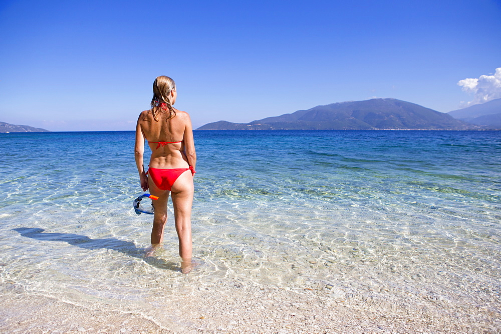 woman , looking out to sea, standing in sea with snorkel, on sunny beach - 786-9986