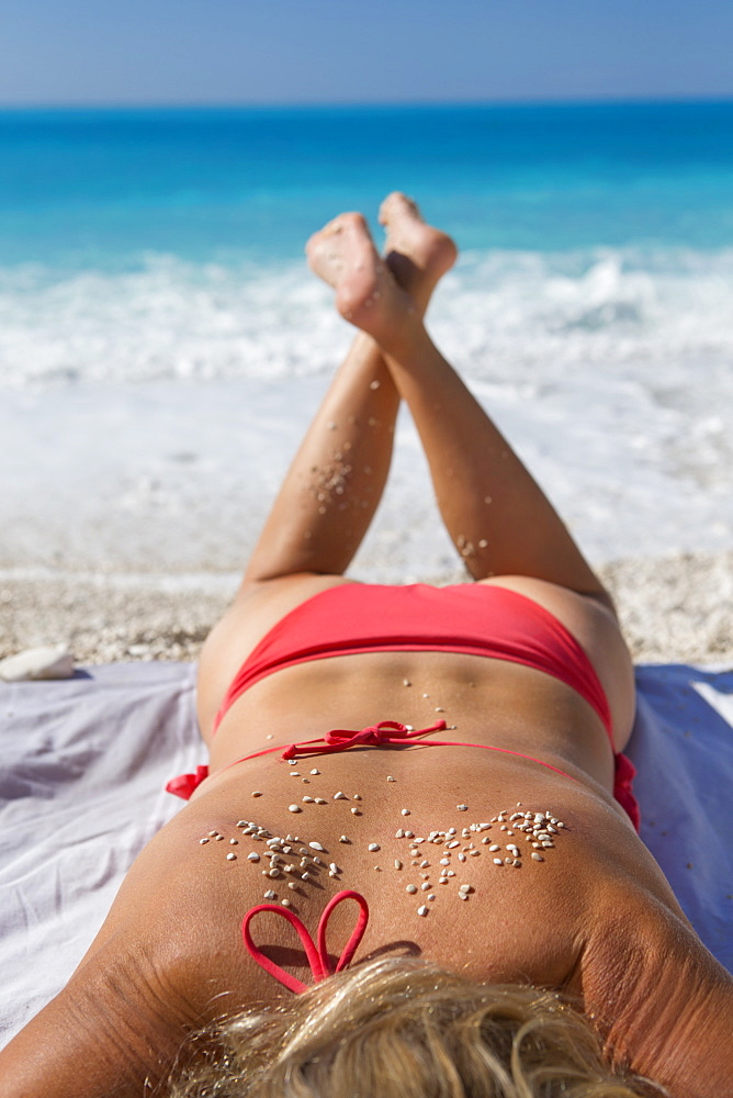 woman, sunbathing with sand on back, on sunny beach