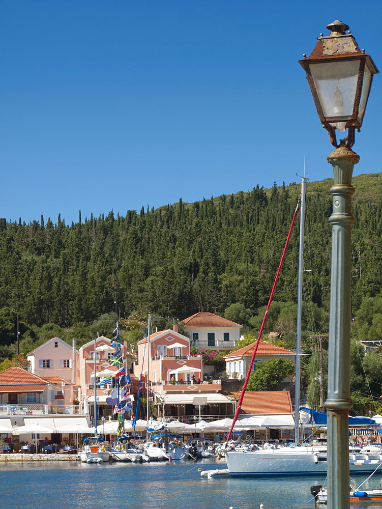 Greece, Kefalonia, Fiskardo, view of lamp and yacht in sunny coastal harbour