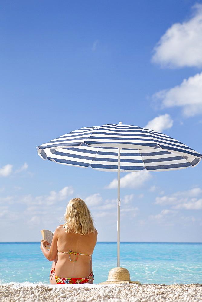 Woman reading book on sunny beach under striped beach umbrella, Greece
