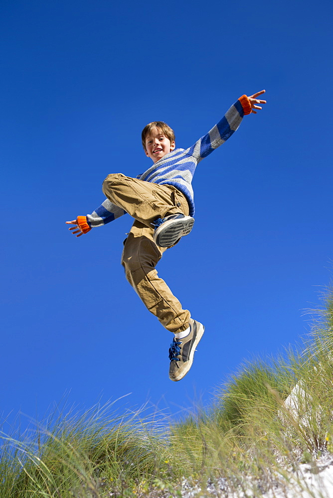 Exuberant boy jumping for joy over sand dune beach grass