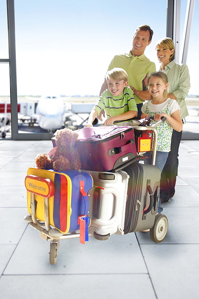 Family With Luggage Trolley In Airport Departure Lounge