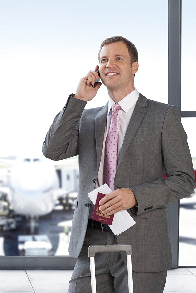 Businessman With Luggage Making Phone Call At Airport