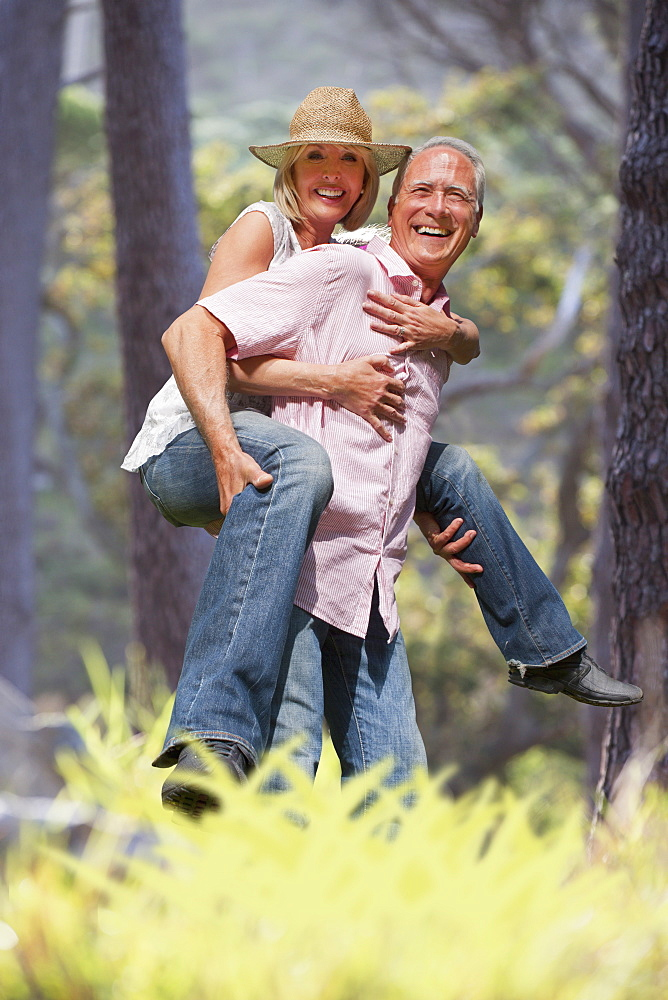 Senior Man Giving Woman Piggyback In Countryside