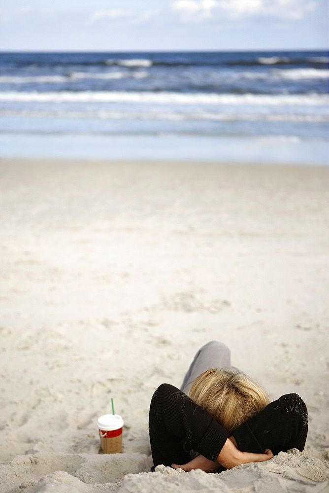 Woman relaxing on sandy beach beside disposable cup, lying on back, hands behind head, looking at horizon over sea, rear view