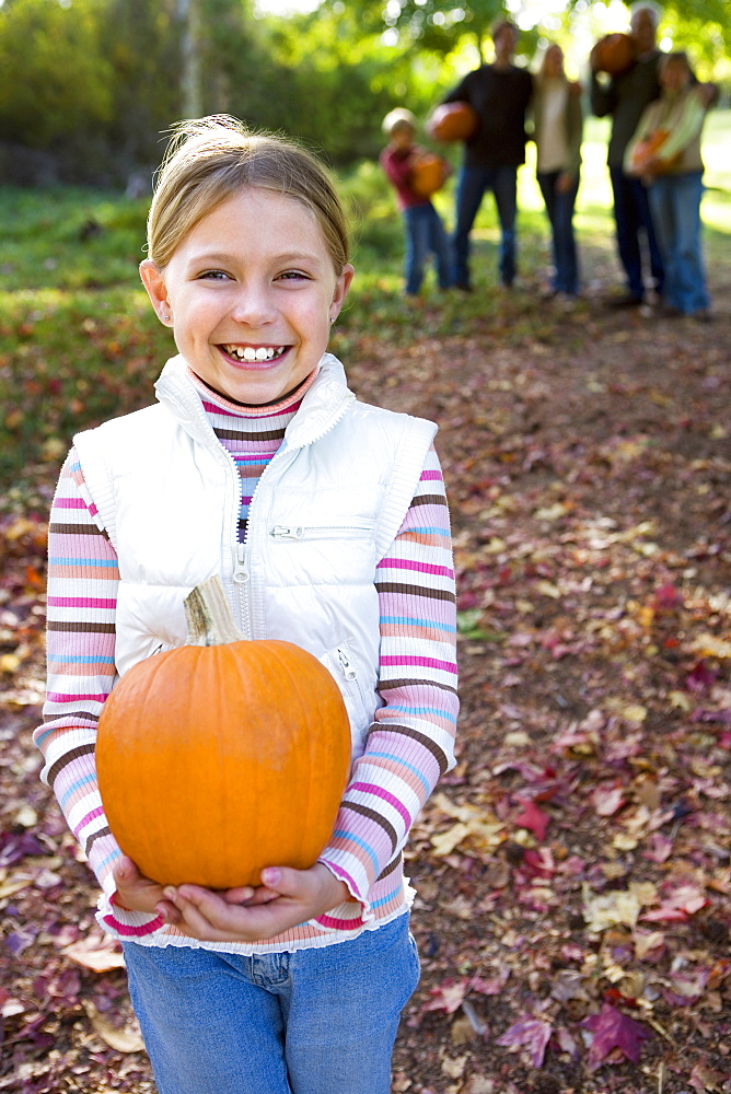 Multi-generational family standing in garden in autumn, focus on girl (6-8) holding pumpkin, smiling, portrait