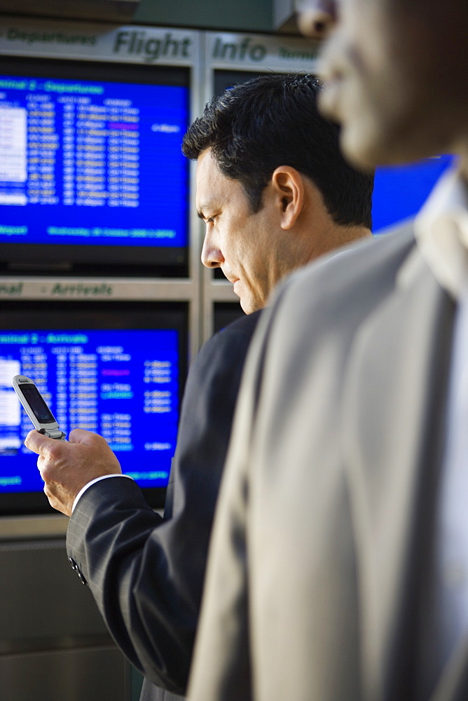 Two businessmen waiting in airport departure lounge, man reading text message on mobile phone  (differential focus)