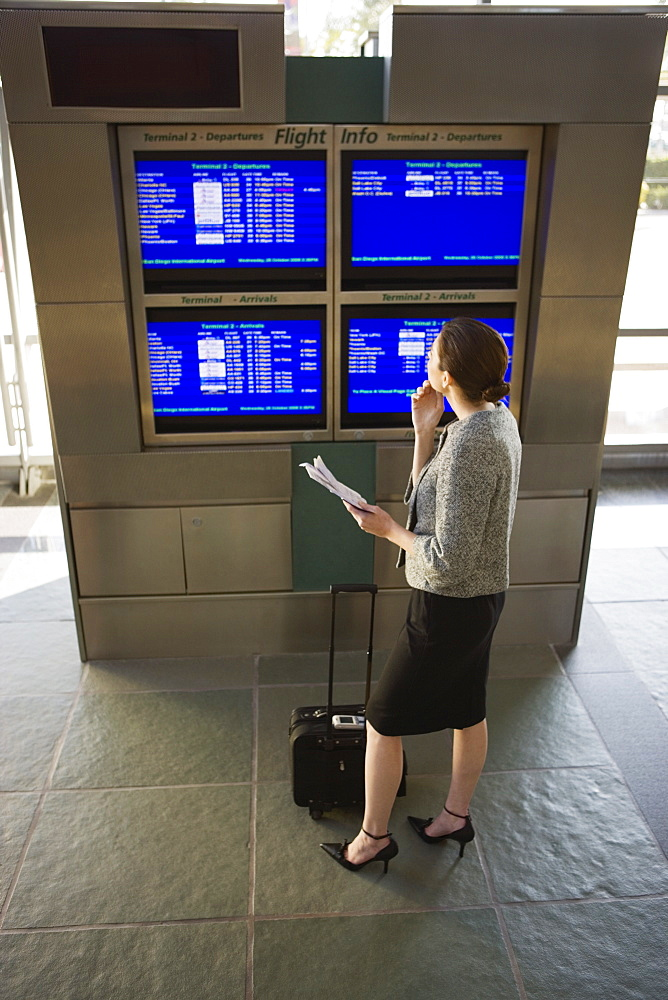 Businesswoman looking at departure times on screen in airport lounge, holding ticket, elevated view