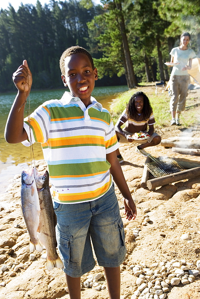 Family cooking food on camping trip beside lake, boy (8-10) holding aloft fish in foreground, smiling, portrait